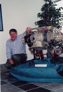 John Knudsen, president for Adams Aircraft Industries, next to the Continental TSIO-550 engine, which powers the CarbonAero.