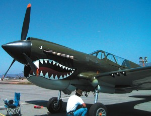 A ferociously fanged Curtiss P-40 gets the attention of a guest at the Wings Over Gillespie airshow in El Cajon.