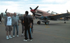 Guests walk around the Chino airshow, oblivious to the fangs on a Curtiss P-40 in the background.