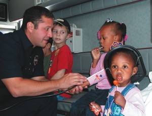 Firefighter Pete Perez demonstrates how a blood pressure cuff works to Octavia Brown, 4, and her sister Jada, 2, both of Aurora.