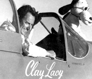 "Clay Lacy and his partner, ""Snoopy,"" pose their P-51 for the A.P. camera. We're not sure whether the designation EXPERIMENTAL on the fuselage applies to the plane or it's mascot. Latter is pylon racing's only ""passenger."""