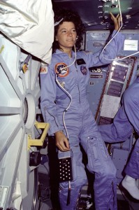 On Challenger's mid-deck, Mission Specialist Sally Ride, wearing light blue flight coveralls and communications headset, floats alongside the mid-deck airlock hatch.