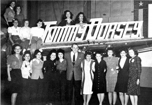 Tommy Dorsey and Republic employees, in Hangar 2, Republic Aviation Corp., with Theresa Rachiele next to Dorsey (in light dress) and Josephine and Sarah (with hand resting on the letter y) directly above him.