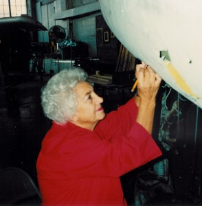 Josephine Rachiele measures an area for a patch on a P-84 being restored at the Cradle of Aviation Museum in Long Island.