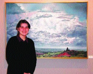 Deborah King, assistant director of Canaan Gallery in Southglenn Mall, with a landscape by Bob Simpich of Colorado Springs.
