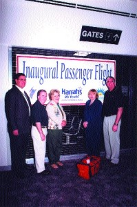 Mayor Hawker (right) and his staff take time for a picture next to the banner signifying Gateway's first commercial passenger flight.