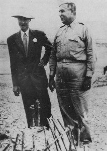 L to R: Nuclear physicist J. Robert Oppenheimer, with Col. Leslie Groves, beside the remains of the tower used to set off the world's first atomic explosion on the Alamogordo bombing range.