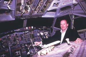 Tom Bennington, president of Max Power, in the cockpit of one of his 727s, displaying a model of a Boeing used as a billboard advertisement.