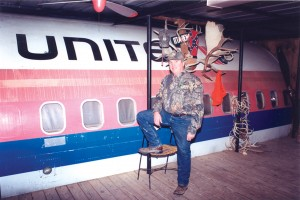 Gary Bright, co-owner of the Boeing 727 Hunting Lodge, on the enclosed wooden porch constructed on the forward starboard side of the fuselage.