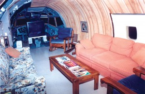 A living room occupies the forward section of the converted airliner. The TV and entertainment center is setup in the former cockpit.