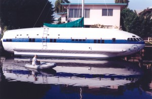 Dave Drimmer pilots a boat next to his Boeing 307 plane boat, at home at the Isle of Venice in Fort Lauderdale.