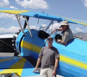 Mike Gillis, in the cockpit of the Bull Stearman, and Dennis Ivans, take a break between flying guests.