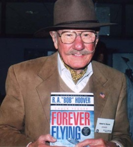"Bob Hoover, holding a copy of ""Forever Flying,"" which tells about five extraordinary decades of aerial escapades."