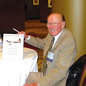 "Bob Hoover, holding up a copy of ""The Quest for Mach 1,"" at the Society of Experimental Test Pilot's annual symposium, 2003."
