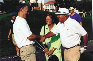 Lee Lauderback and Arnold Palmer shake hands, as Palmer's fiancée, Kit Gawthrop, looks on.
