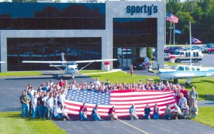Sporty's employees in front of building with American Flag Based at Clermont County Airport, Sporty's has 200 employees.
