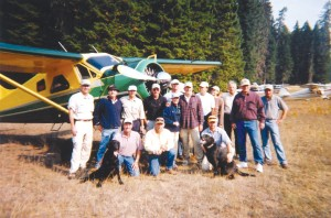 In September 2003, Greg Anderson (far left, standing) participated in the Fourth Annual Backcountry Aerial Safari. Another participant was Harrison Ford (top row, fourth from left.) Ford's de Havilland Beaver is in the immediate background.