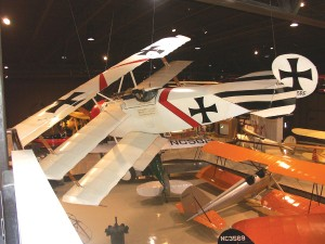 In silent flight over a Curtiss JN-4 Jenny is a nearly exact replica of a Fokker Dr. 1 Dreidecker, wearing the white, black and red markings of Jasta 11, the squadron of the Red Baron, Manfred von Richthofen.