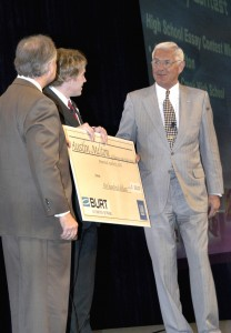 L.G. Chavez Jr., president, Burt Automotive Network, and Robert Lutz, vice chair of global product development, General Motors, present high school student Austin Melton with a scholarship for his winning essay.