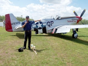"Kermit Weeks points to a two-place North American P-51 Mustang, ""Sizzlin' Liz,"" that flew in for the Mustangs and Mustangs event at Fantasy of Flight."