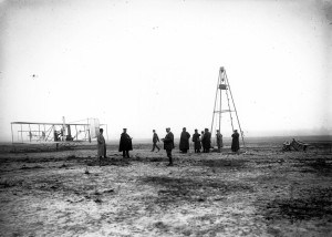 In one of the amazing images among the 1908 glass-plate negatives the museum acquired last year, Wilbur Wright (distant figure in the center) strides toward his Flyer. The man to his right with the newspaper is the Wrights' European agent, Hart O. Berg