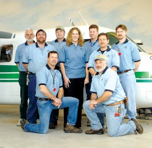 Installation experts at XN Avionics in Spokane include, L to R: (standing) Axel Armbruster, Vaughn Burgess, Phil Carlson, Kristi Harvie, Jeff Pugh, Scott Manina and Robert Maahs, with (kneeling) John Hale and Jeff Hartley.
