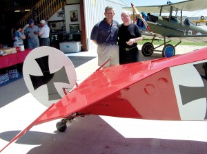 L to R: Andy Parks presents Jerry Priddy with an honorary membership into the LaFayette Flying Corps at the Colorado International Aviation Museum, A Fokker Dr.1 and SE5A are nearby.