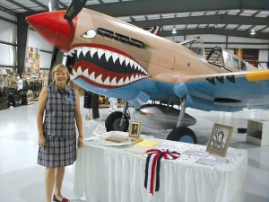 "Sue Paul, executive director of the Warhawk Air Museum, with the Curtiss P-40 that was featured in the movie ""Pearl Harbor"" with a 48-star U.S. flag in the background."