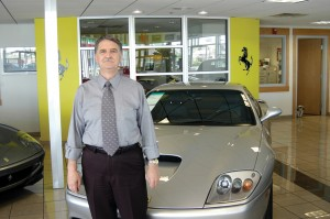 Bill Stewart, owner of Ferrari of Denver, in front of a Ferrari 575.