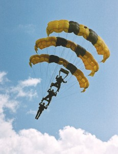 Three members of the Army Golden Knights Parachute Team drift in for a landing, one on top of the other.