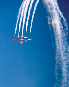 The Canadian Snowbirds come out of one of their spectacular maneuvers trailing smoke.