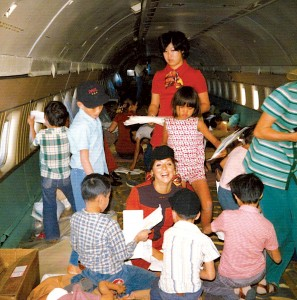 World Airways flight attendants Carol Shabata (standing) and Valerie Witherspoon (kneeling) play with the Vietnamese orphans on the historic evacuation flight on April 2, 1975.