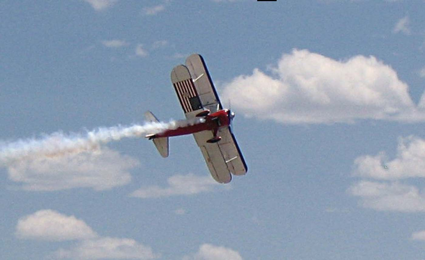 The aerobatic Stearman owned by Greg Shelton displays its patriotic underside as it completes a low altitude roll.