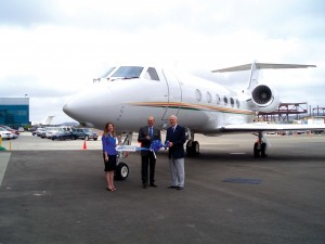 L to R: Megan Cunningham, Jet Source charter services manager, Frank W. Milian Jr., Jet Source president and COO, and Ted Owen, Carlsbad Chamber of Commerce president and CEO, get ready to cut the ribbon.