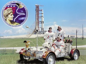The prime crew for Apollo 17: Eugene A. Cernan, commander (seated in the lunar roving vehicle trainer); command module pilot Ronald E. Evans (standing on right); and lunar module pilot, Harrison H. Schmitt. The Apollo 17 Saturn V is in the background, and