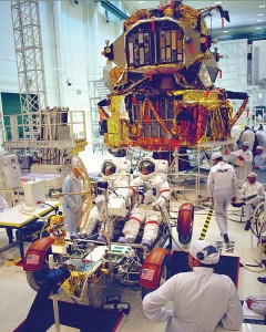 "Eugene Cernan and Harrison H. ""Jack"" Schmitt prepare the lunar roving vehicle and the communications relay unit mission simulation. Standing to the left, support team astronaut Gordon Fullerton discusses test procedures to be performed."