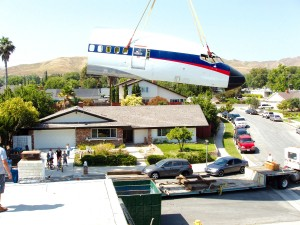 A giant crane lifts the 10,000-pound, 35-foot-long portion of a 727 fuselage high above the Penikas' house, and lowers it into their back yard.