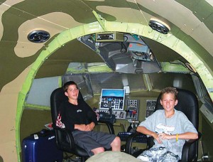 "L to R: Tommy and Justin Penikas agree that working with the flight simulator system in the cockpit of their own 727 aircraft is a ""cool"" thing to do."