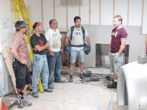 "On day one of the ""Aviation House"" project, Steve Watson discusses ways to turn an ordinary room into a pilots' lounge with builders L to R: Matthew Potter, Steve Rapak, Les Delinski and Dan Golden."