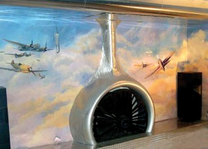 "The custom-made aluminum fireplace in the ""pilot's lounge"" is fashioned from a real airplane engine. A projection screen can be lowered from the airplane wing fastened across the ceiling. The colorful wall mural adds to the aviation theme, while pilots' l"