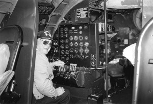 "Crew chief Dale Nicholson takes the controls in the flight engineer's station. Nicholson has been on the B-29 project since ""T-Square-54"" arrived from Lowry AFB. He trained as a flight engineer on the B-29 during World War II."