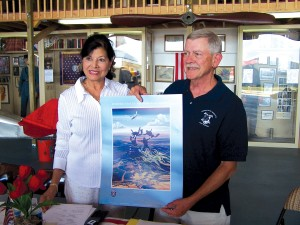 Bea Khan Wilhite, CAHS president, accepts one of many works of aviation art donations from artist Richard Broome.