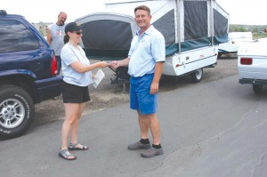 Ray Reeves, owner of Adventure Camper Rentals, hands Lena Lippert the keys to a Fleetwood Tent Trailer to visit Grand Lake.