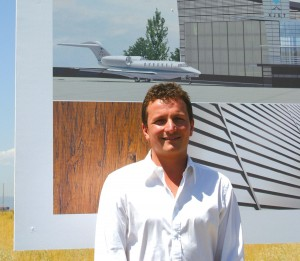 Xjet CEO Josh Stewart stands in front of the club's sign where the future facilities will stand. Completion of the hangars is expected around April 2006.