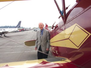 Clayton Scott poses with this 1928 Travel Air (at Boeing Field), a plane similar to the 1927 Travel Air he flew for Vern Gorst's Seattle Flying Service in 1928. At the left is the twin-engine Piper Aerostar he flew into Boeing Field for his 100th birthday