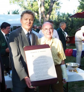 Federal Republic of Germany Honorary Consul Bernhard Bleise and Jerry Priddy show a copy of the Instrument of Surrender.