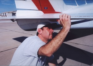 Ken Moskowitz does a pre-flight inspection on a Piper Aztec carrying supplies for the victims of Hurricane Katrina.