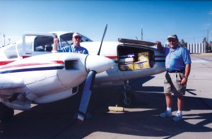 L to R: Tim Barrios inspects his engine as Lynn Kusy, executive director of Williams Gateway Airport, checks out the supplies loaded in the aircraft's nose.