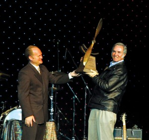 "Burt Rutan smiles as he accepts the Wings Over the Rockies ""Spreading Wings"" award from Gregg Moss, 9NEWS business reporter and gala master of ceremonies."