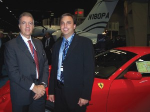 L to R: Piero Ferrari, president of Piaggio Aero, meets with Steven Santo, CEO of AvantAir, by a Ferrari supercar, with the new Piaggio Avanti II in the background.